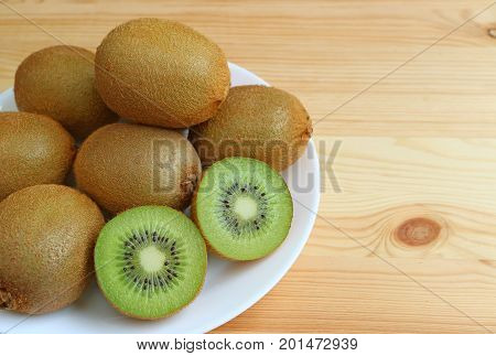 Plate of many fresh ripe whole fruits and cross-sections of kiwi fruits on wooden table, with free space for design and text