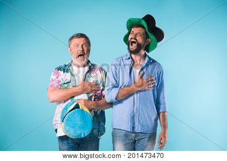 The two football fans singing the national anthem over blue background
