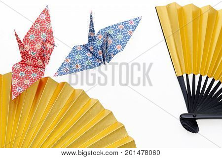 golden folding fan and origami bird isolated on white background