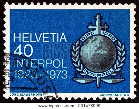 SWITZERLAND - CIRCA 1973: A stamp printed in Switzerland issued for the 50th anniversary of International Criminal Police Organization (Interpol) shows Interpol emblem, circa 1973.