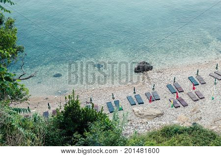 ULCINJ, MONTENEGRO - JULY 30, 2017: Small rock beach Liman on the Adriatic Sea in Ulcinj, Montenegro. Early morning time with empty beach beds, closed umbrellas and without people.