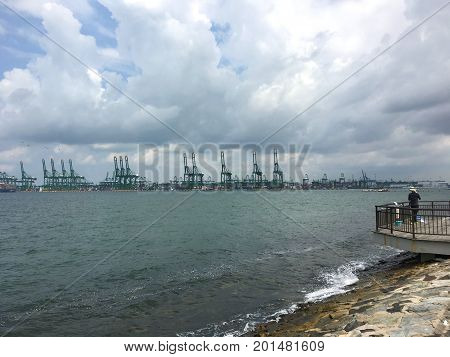 Fisherman in front of Singapore commercial port and cranes