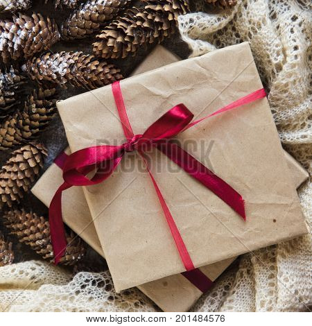 Kraft Gift Box With Red Ribbon Bow On Winter Holidays Background Of Pine Cones Powdered With Artific