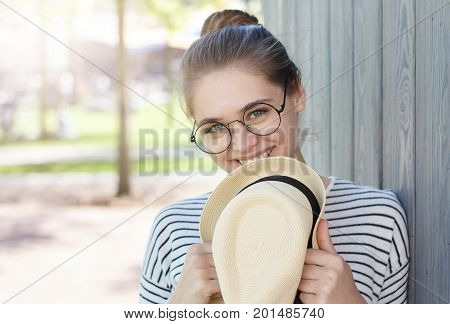 Outdoor Photo Of Pretty Positive Lady In Round Eyeglasses, Holding Straw Hat With Black Ribbon In Ha