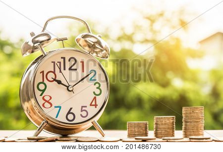 Clock alarm and step of coins stacks with nature background money saving and investment or family planning concept over sun flare silhouette tone.