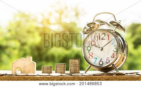wooden house model and step of coins stacks with clock alarm nature background money saving and investment or family planning concept over sun flare silhouette tone.