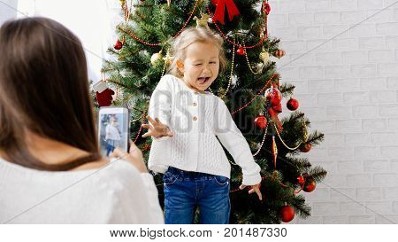 Mother making photo with smart phone of her little daughter near christmas tree. Baby girl funny posing and playing the ape for photography.