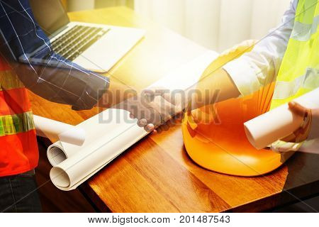 Handsome construction workers in protective helmets and vests are shaking hands while working in the office center, Horizontal, Blurred background