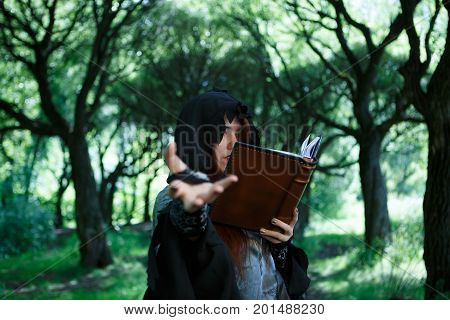 Picture of witch with spell book, outstretched hand in dark forest, blurred background