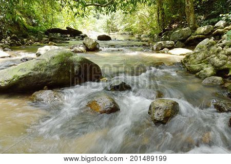 river flowing on cataract and water splashing in forest