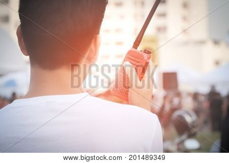 Man with a Walkie Talkie or Portable radio transceiver for communication at event