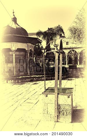 Garden in the courtyard of Muslim mosque in the old city of Akko. Al-Jazzar mosque as fine example of the Ottoman architecture in old Acre Israel. Vintage style toned picture