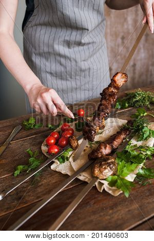 Waiter takes off grilled meat from skewer. Field mushrooms and cherry tomatoes with lavash, barbecue and natural food preparing in restaurant