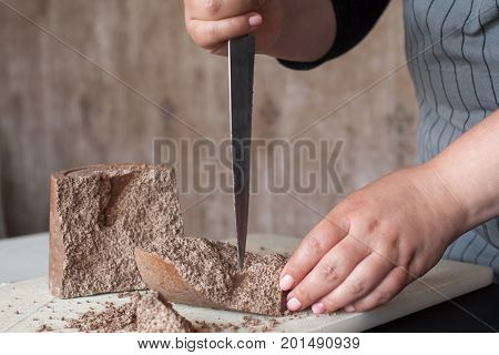 Cook breaks off piece of aerated chocolate for decoration of delicious desserts in restaurant. Process of making culinary art, close up picture