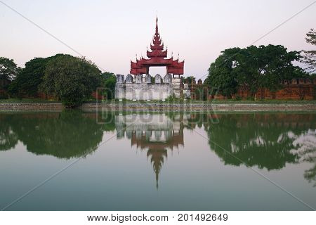 Ancient bastion of the old city with reflection in gray twilight. Mandalay, Burma (Myanmar)