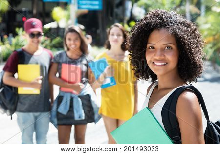 Beautiful african american female student with group of international students outdoor in the city in the summer