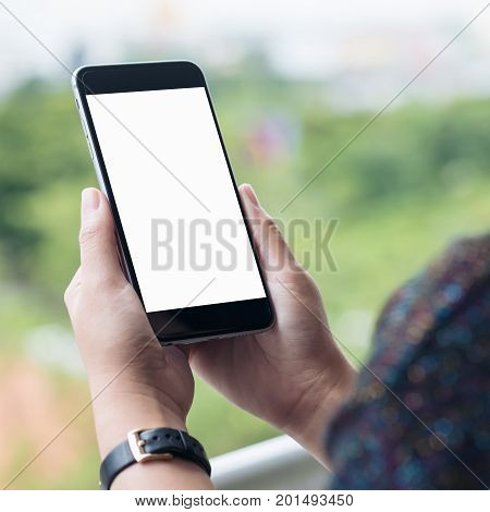 Mockup image of a woman's hand holding and using black smart phone with blank white screen while standing at the balcony of a high building with metal rail and blur green nature background