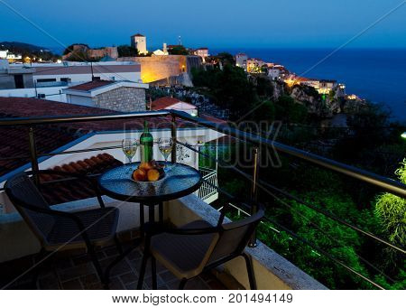 Table with bottle of white wine two glasses and fruits on balcony with beautiful view on sea and Stari Grad at twilight scene. Romantic celebration of engagement or anniversary. Ulcinj Montenegro.