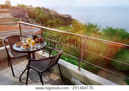 Table with fresh delicious breakfast with pastry coffee orange juice and fruits served on balcony with beautiful view on sea and Stari Grad Ulcinj Montenegro. Place for romantic holiday.