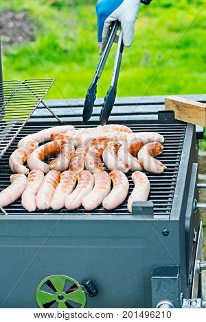 Some Brat sausage are on the charcoal grill