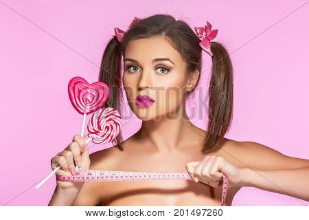 beautiful young woman with pink makeup and girly ponytails holding two sweet  lollypop and measuring tape. beauty shot on pink background. copy space.