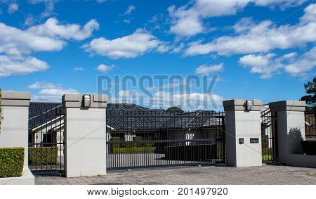 Black metal driveway entrance gates set in brick fence with large house in background