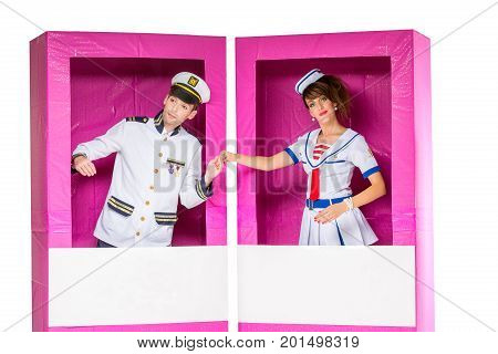 beautiful young couple looking like dolls standing in big pink doll box. Isolated on white background.