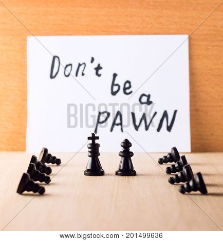 The king with the queen and the servants bowing before them against the background of the inscription in English do not be a pawn