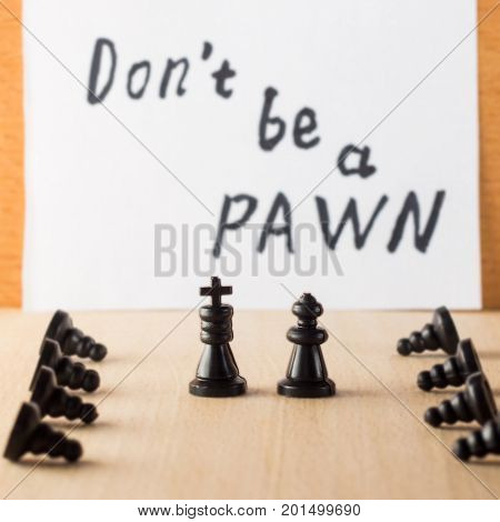 Bowed servants in front of managers chess pieces king queen and pawns symbolizing people of different statuses against the motivating inscription in English do not be a pawn