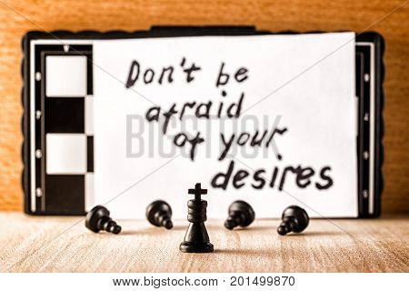Black chess king servants bowing before him and motivating the inscription in English do not be afraid of their desires