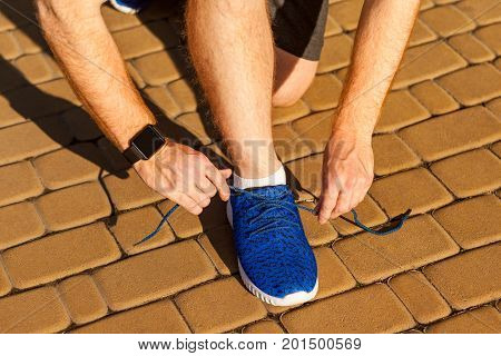 Tie shoelaces. Blue sneakers. Sport. closeup of human hands tying sport shoes.