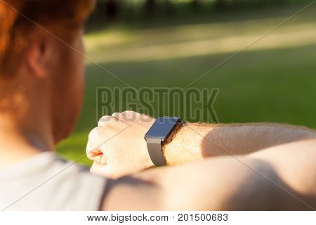 Redhead athlete watching in smart wath or fitness tracker. Summer morning outdoor