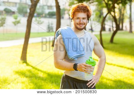 Happiness redhead athlete holing bottle and towl smiling and looking at camera. Outdoor