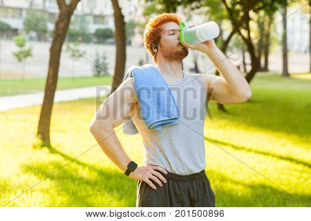 Young adult redhead and freckles man drink water after cross and closed eyes. Outdoor