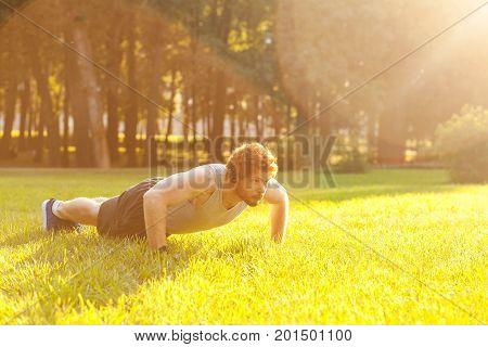 Push ups. Sunny. Summer. Redhead and bearded fitness model doing push ups. Outdoor