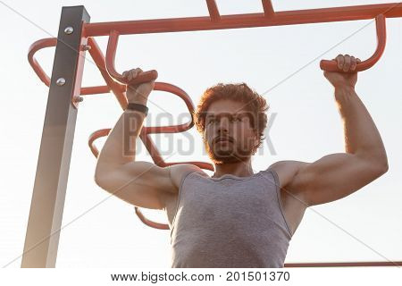 Pull ups in orizontal bars. Young adult bearded redhead man doing pull ups. Outdoor
