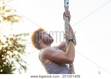 Climed higer and higher. Ginger sportsman doing exercise at rope. outdoor shot