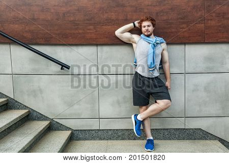 Fitness sport. Bearded redhead man in sportswear doing yoga fitness exercise in the street outdoor sports urban style
