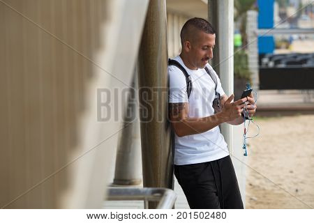 Positive young guy using smartphone with hanging earphones outdoors. Addicted sporty man leaning on column while surfing net. Stroll concept