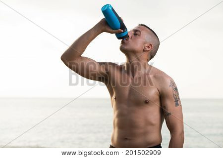 Shirtless muscled young man drinking eagerly water after vigorous exercise outdoors. Strong male athlete with tattoo closing eyes to enjoying refreshment. Water as source of energy concept