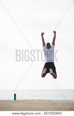 Rear view of sportsman jumping for joy outdoors. Excited young man with raised arms leaping and enjoying healthy lifestyle. Winning concept