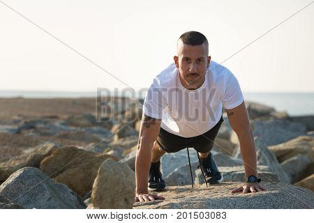 Sporty handsome bald athlete preparing for push-ups and holding his weight on hands. Confident fitness training doing exercise on shore and looking at camera. Effort concept
