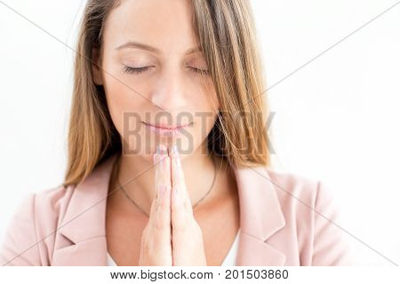 Close-up of serene face of young Caucasian businesswoman praying in silence