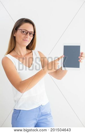 Portrait of confident young Caucasian businesswoman wearing glasses holding touchpad and pointing at screen