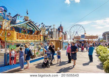 Cardiff United Kingdom - August 26 2017: People enjoying themselves on a sunny day at the Cardiff Bay Beach Fair an urban seaside beach fair at Roald Dahl Plass in Cardiff Bay Cardiff.