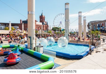 Cardiff United Kingdom - August 26 2017: Children and families are enjoying zorb balls bumper cars and other activities at Cardiff Bay Beach fair at Roald Dahl Plass in Cardiff Bay Cardiff.