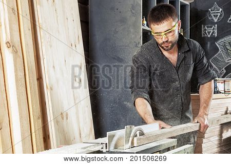 Man Cutting Wood With A Circular Saw