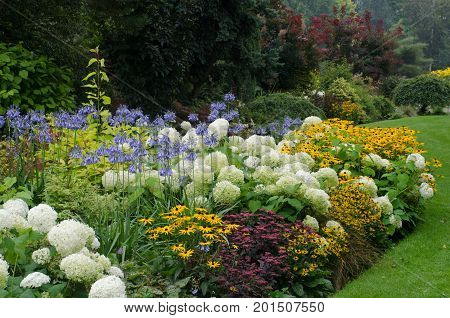 Large English perennial border in traditional garden
