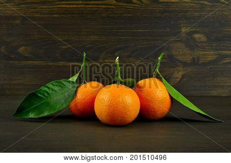 Mandarin oranges with green leaves on dark wood background