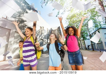 Diverse group of school kids throwing piles of paper happy exiting building
